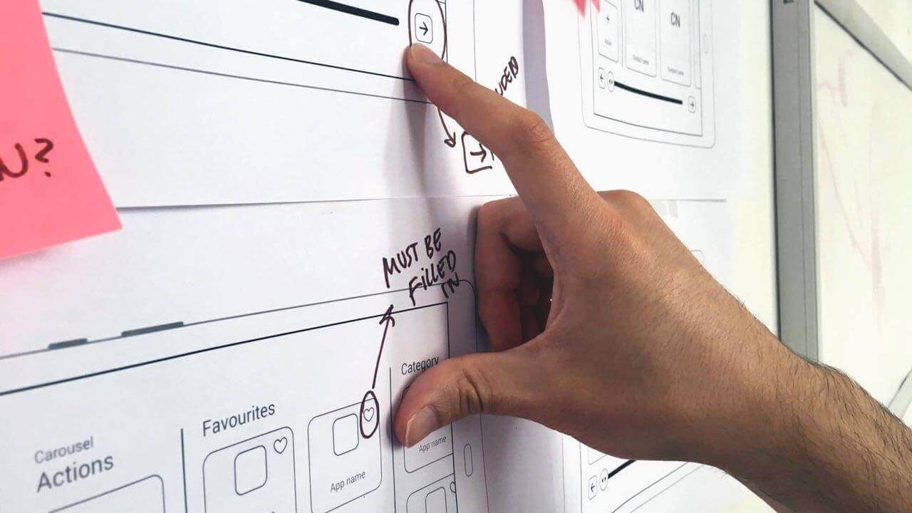 Hand pointing at user experience (UX) wireframes of Breezie's features.